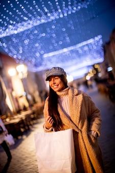 추운 크리스마스 밤 거리에서 아름 다운 젊은 여자
