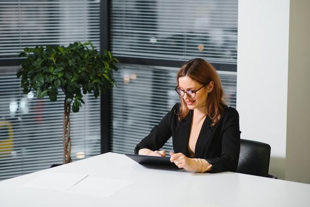 Красивая молодая женщина на рабочем месте с помощью цифрового планшета