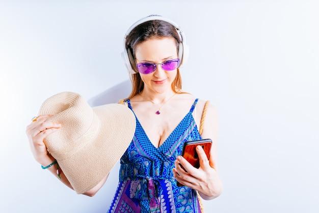 흰색 바탕에 아름다운 젊은 여성이 여름 안경과 무선 헤드폰을 끼고 모자를 쓰고 있는 스마트폰을 보고 있습니다. 여름 방학 열 개념