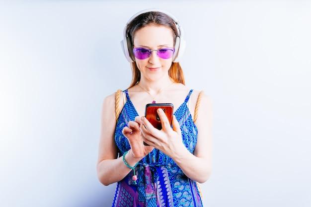 흰색 바탕에 여름 안경을 쓰고 스마트폰을 보고 있는 무선 헤드폰을 쓴 아름다운 젊은 여성. 그녀의 컨셉은 휴가를 간다. 권하다. 복사 공간이 있는 광고