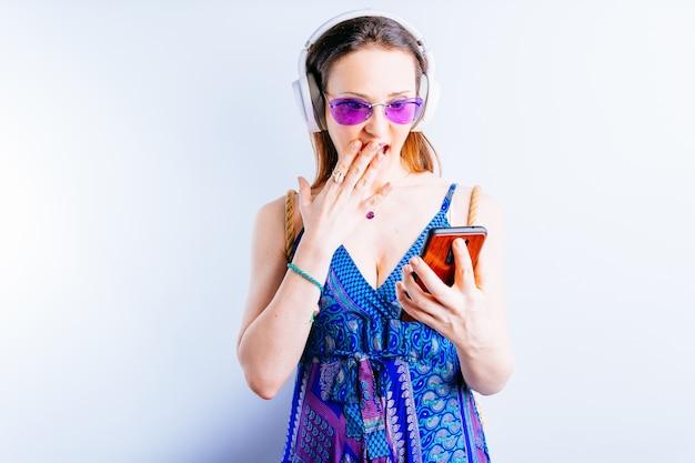 흰색 바탕에 아름다운 젊은 여성이 여름용 안경과 무선 헤드폰을 끼고 스마트폰을 보고 깜짝 놀라고 있습니다. 그녀의 컨셉은 휴가를 간다. 권하다. 복사 공간이 있는 광고