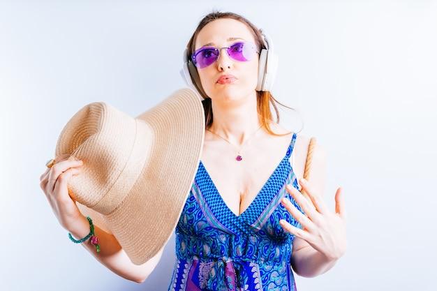 흰색 바탕에 아름다운 젊은 여성이 여름용 안경을 쓰고 모자가 부글부글 끓어오르는 듯한 무선 헤드폰을 쓰고 있습니다. 여름에 개념 과열입니다. 여름 방학