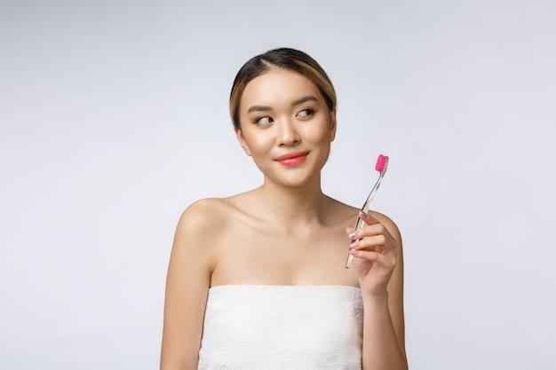 격리 된 흰색 배경에 아름 다운 젊은 여자는 칫 솔, 아시아를 보유하고