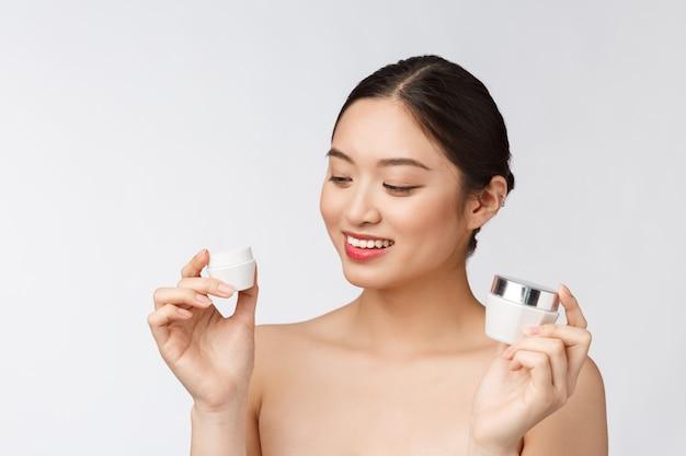 화장품 얼굴 크림을 들고 흰색 격리 된 벽에 아름 다운 젊은 여자, 아시아