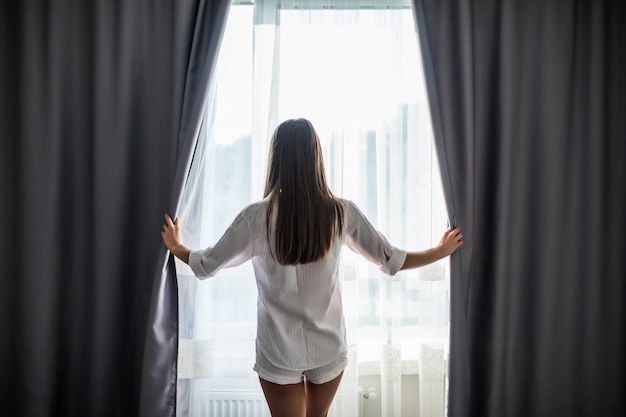 Beautiful young woman opening curtains and looking through the window
