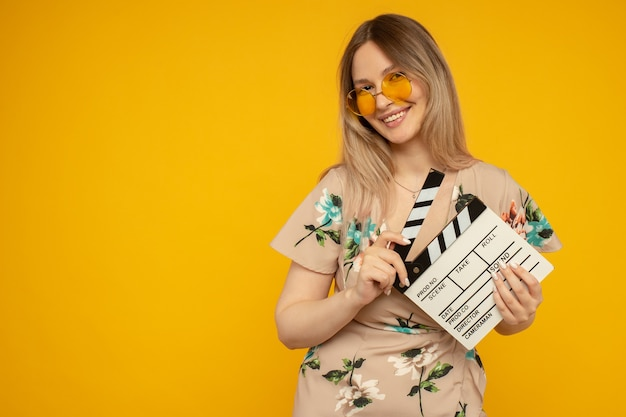Beautiful young woman in orange eyeglasses holding classic white film making clapperboard isolated on yellow background. people sincere emotions, lifestyle concept. advertising area
