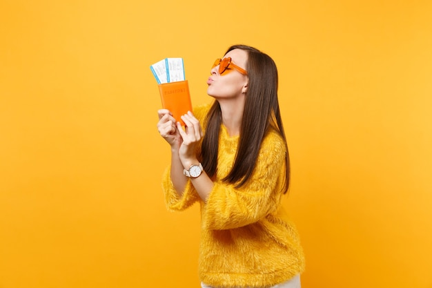 Beautiful young woman in orange heart glasses blowing lips sending air kiss holding passport, boarding pass tickets isolated on yellow background. people sincere emotions, lifestyle. advertising area.