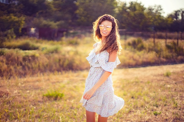 Beautiful young woman outdoor on the hill on a summer day