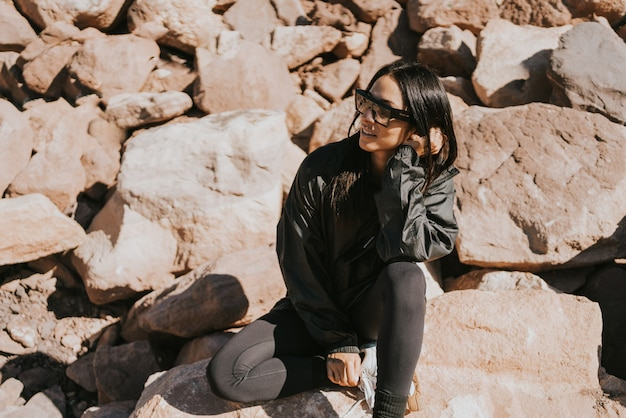 Beautiful young woman outdoors wearing sunglases enjoying the sun sitting on a pile of rocks and smiling