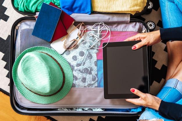 大きなスーツケースに荷物を詰め込んだ美しい若い女性。上から撮影。ハイアングルビュー。旅行準備のコンセプト