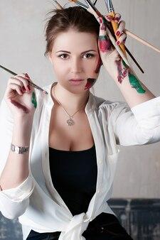 Красивый художник молодой женщины в ее студии