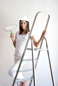 Красивая молодая женщина красит квартиру