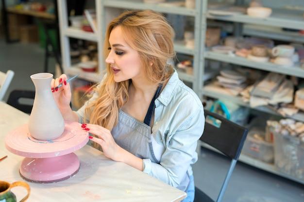 美しい若い女性が陶器のワークショップで粘土の水差しを描く