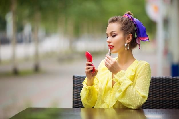 美しい若い女性は口紅で唇を描く