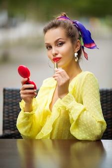 Красивая молодая женщина красит губы помадой