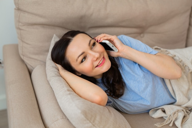 Beautiful young woman in pajamas lies on the couch with a mobile phone at home