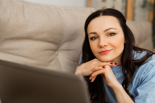 Beautiful young woman in pajamas lies at home on the couch with a laptop