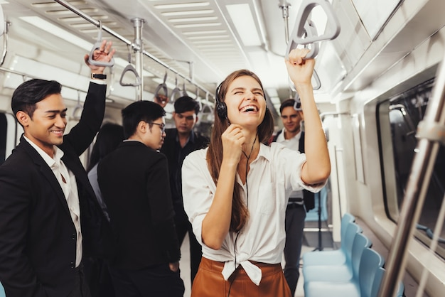 Beautiful young woman passenger standing with headphones and while shirt in the modern subway train
