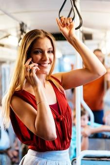 電車の中で彼の携帯電話を使用して美しい若い女性の乗客。モバイルのコンセプト。