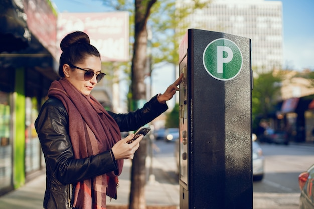 Beautiful young woman pays for parking in meter on the street