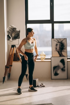 Beautiful young woman performs exercises at home