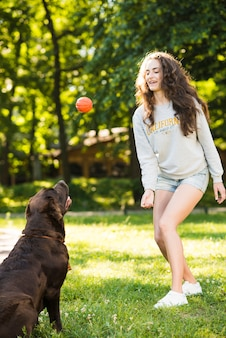 Beautiful young woman playing ball with her dog in garden