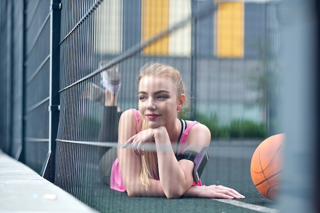 Beautiful young woman playing basketball outdoors. the girl on the sports ground