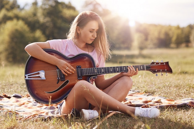 Beautiful young woman playing gitar in meadow, has stright blonde hair, looks concentrated on musical insrtument, wearing casual clothes, spending time alone, enjoying wonderful nature. outdoor shot