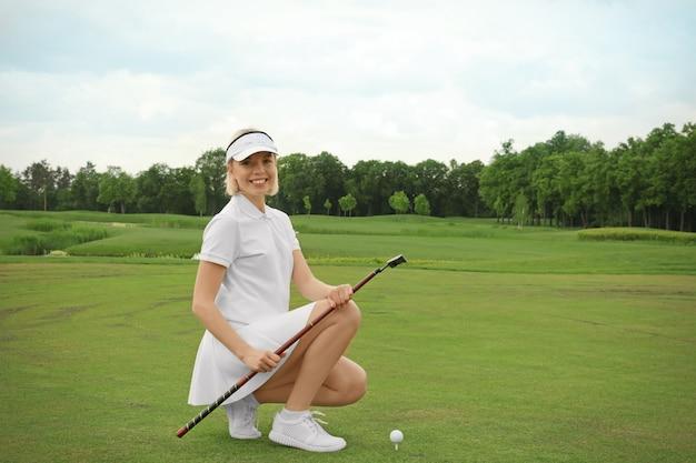 Красивая молодая женщина, играя в гольф на поле в летний день