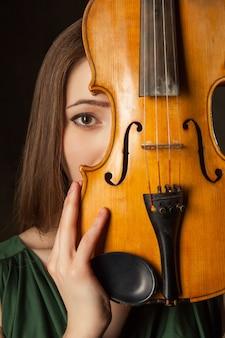 Красивая молодая женщина играет на скрипке на черном фоне