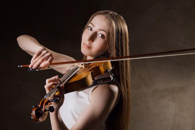 검정 배경 위에 바이올린을 연주하는 아름다운 젊은 여성