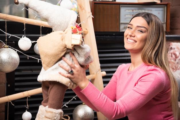 家で人形で遊ぶ美しい若い女性。