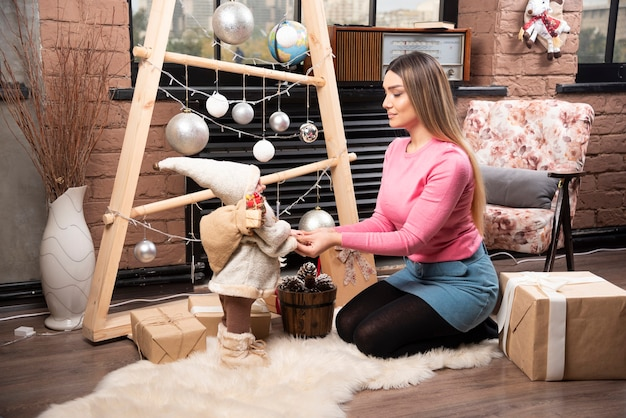 Beautiful young woman playing with doll at home.