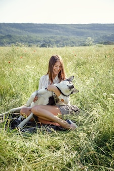 Beautiful young woman playing with funny husky dog outdoors at park
