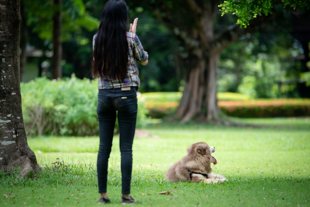 Beautiful young woman playing with her little dog in a park outdoors. lifestyle portrait.