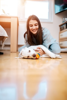 Beautiful young woman playing with her puppy at home.
