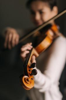 Красивая молодая женщина играет на скрипке у себя дома, в комнате с современным уютным интерьером. фокус камеры на скрипке.