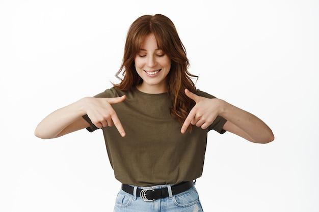 행복한 얼굴로 가리키고 아래를 내려다보는 아름다운 젊은 여성, 흰색으로 서 있는 재미있는 광고를 발견했습니다.