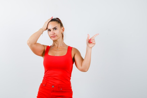 Beautiful young woman pointing up, holding hand on head in red tank top, pants and looking troubled , front view.