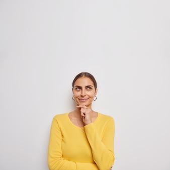美しい若い女性は何かが考えを深く考えている上に焦点を当てたあごに手を保つことを熟考します灰色の壁の上に隔離されたカジュアルな黄色のジャンパーを着ています