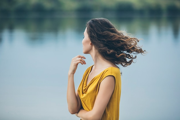 Beautiful young woman portrait near the lake in a bright dress