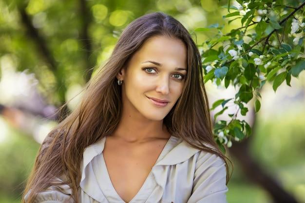 屋外の公園で開花するリンゴの木の枝の横にある美しい若い女性の肖像画
