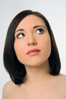 Портрет красивой молодой женщины на сером фоне