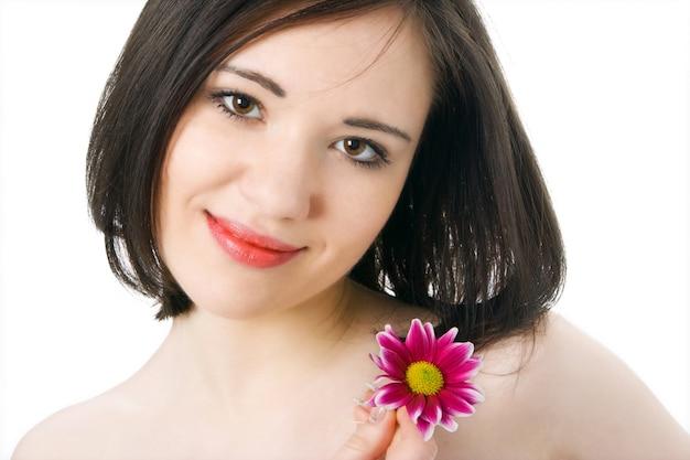 Портрет красивой молодой женщины с цветком хризантемы на сером фоне