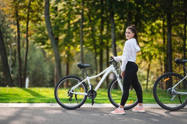 白い自転車でポーズをとって美しい若い女性