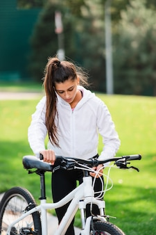 흰색 자전거에 포즈를 취하는 아름 다운 젊은 여자