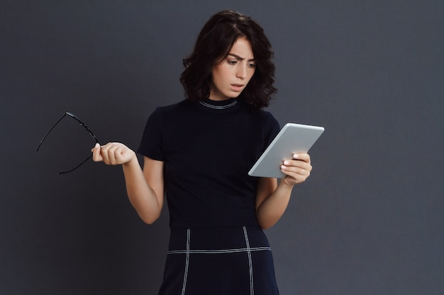 Beautiful young woman posing over grey wall holding tablet and glasses in hands