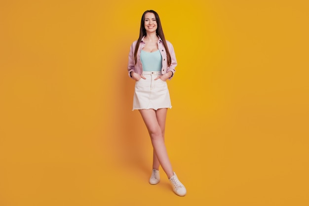 Красивая молодая женщина позирует руками в карманах, изолированных на желтом фоне.