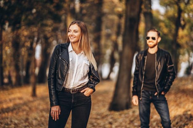秋の公園でポーズ美しい若い女性。背景は彼氏のぼやけたシルエット