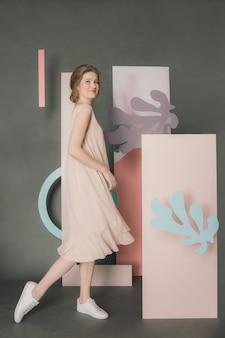 灰色の背景にスタジオ インスタレーションの前でポーズをとる美しい若い女性